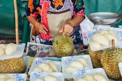 Kvinnan klipper durianen på marknaden fotografering för bildbyråer