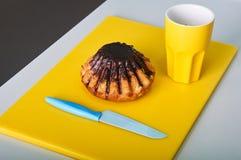 Kvinnan klipper en muffin Arkivbild