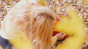 Kvinnan klipper en pumpa i hans gård Gula lönnlöv i förgrunden arkivfilmer