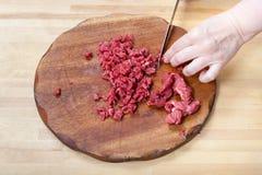 Kvinnan klipper kött på träskärbräda Royaltyfria Bilder