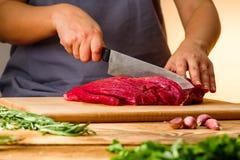 Kvinnan klipper nytt kött i köket royaltyfri bild