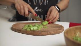 Kvinnan klipper selleri på en skärbräda för att laga mat hemlagad grönsaksallad stock video
