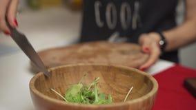 Kvinnan klipper selleri på en skärbräda för att laga mat hemlagad grönsaksallad arkivfilmer