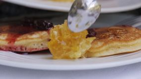 Kvinnan klipper till stycken pannkakorna på en platta och äter dem lager videofilmer