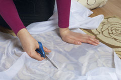 Kvinnan klipper tyget med sax för att sy gardiner på fönstret Tyget ligger på golvet ovanför sikt royaltyfri bild