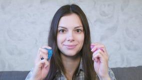 Kvinnan knådar, pressar och sträcker en rosa och blå slam Kvinnan spelar med slam Tuggninggummi stock video