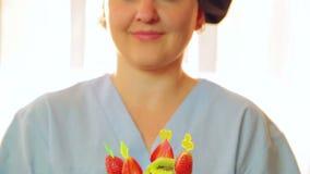 Kvinnan - kocken ler och rymmer en platta med en fruktefterrätt i henne händer Kontrollsolljus från fönstret Närbild stock video