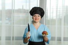 Kvinnan kocken rymmer i en hand en frukt av mango och i annan hand en kniv Arkivfoto