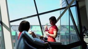 Kvinnan konsulterar på instruktören går hittills på en löparbana stock video