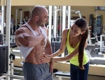 Kvinnan kontrollerar buk- muskler Arkivfoton