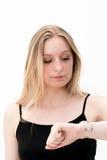 Kvinnan kontrollerar tid på henne armbandsuret Royaltyfria Bilder