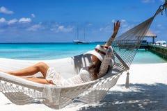 Kvinnan kopplar av i en hängmatta på en tropisk strand arkivbild
