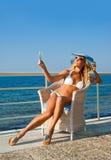 Kvinnan kopplar av i fåtölj på medelhavs- kust Royaltyfri Foto