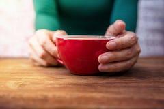 Kvinnan kopplar av i kafét eller huset, kaffekopp i hand på trätabellen Royaltyfria Foton