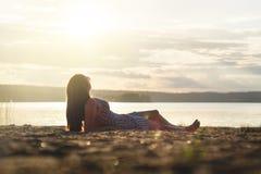 Kvinnan kopplar av och lägger ner i solnedgången på stranden royaltyfri foto