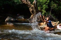 Kvinnan kopplar av och spela i Wang Takhrai Waterfall på Nakhon Nayok Thailand Arkivfoton