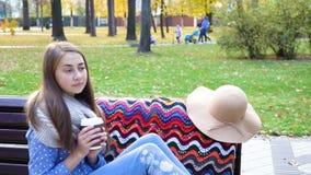 Kvinnan kopplar av på bänken i härliga Green Park med koppen kaffe Video rörelse den attraktiva flickan sitter på ett trä lager videofilmer