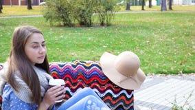 Kvinnan kopplar av på bänken i härliga Green Park med koppen kaffe Video rörelse den attraktiva flickan sitter på ett trä stock video