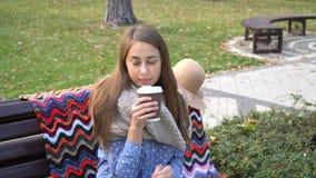 Kvinnan kopplar av på bänken i härliga Green Park med koppen kaffe video rörelse 4K den attraktiva flickan sitter på ett trä arkivfilmer