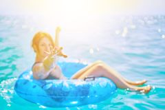 Kvinnan kopplar av på den uppblåsbara cirkeln i havet arkivbilder