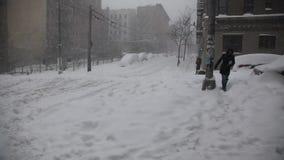 Kvinnan korsar gatan under häftig snöstorm arkivfilmer