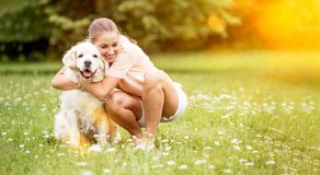 Kvinnan kramar golden retrieverhunden royaltyfria bilder
