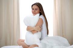 Kvinnan kramar upp kudden efter vak och att skriva in en avkopplad dag som är lycklig och efter sömn för bra natt Söta drömmar, b royaltyfria bilder