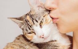 Kvinnan kysser en katt Arkivbild