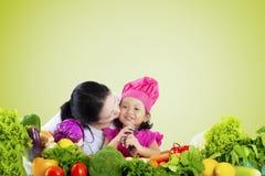 Kvinnan kysser hennes barn med grönsaker på tabellen Arkivbild