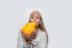 Kvinnan kysser moneybox Arkivfoto
