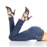 Kvinnan lägger benen på ryggen att ligga med jeans och sandalhäl som pekar upp Arkivfoto