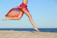 Kvinnan lägger benen på ryggen banhoppning på den lyckliga stranden Fotografering för Bildbyråer