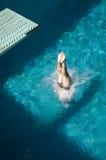 Kvinnan lägger benen på ryggen dykning in i slå samman Arkivbilder