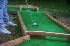 Kvinnan lägger benen på ryggen, golfspelet på gräsplanen, kvinnan som sätter bollen Finalskott, golf royaltyfria bilder