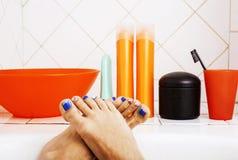 Kvinnan lägger benen på ryggen i badrum med lotten av stilfullt material för omsorg som är pedic fotografering för bildbyråer