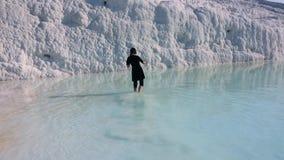 Kvinnan lägger benen på ryggen i det flödande vattnet i Pamukkale stock video