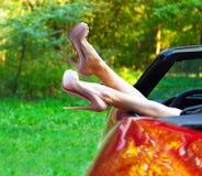 Kvinnan lägger benen på ryggen i höga häl ut fönstren i bil Royaltyfri Foto