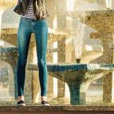 Kvinnan lägger benen på ryggen i utomhus- tillfällig stil för grov bomullstvillbyxa Arkivfoton