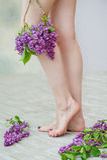Kvinnan lägger benen på ryggen och lilablommor Royaltyfria Bilder