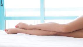 Kvinnan lägger benen på ryggen på sängen i vit sängkläder mot en ljus fönsterbakgrund, skönhetlivsstilbegrepp royaltyfri foto
