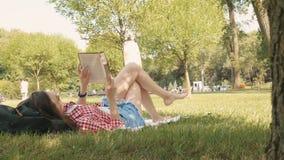 Kvinnan lägger ner eller koppla av på läseboken för grönt gräs i sommar eller fjädrar arkivfilmer