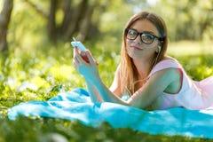 Kvinnan lägger ner eller koppla av på lyssnande musik för grönt gräs med smartphonen i sommar eller fjädrar Royaltyfria Foton