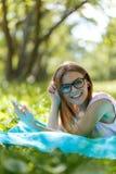 Kvinnan lägger ner eller koppla av på lyssnande musik för grönt gräs med smartphonen i sommar eller fjädrar Arkivbilder