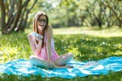 Kvinnan lägger ner eller koppla av på lyssnande musik för grönt gräs med smartphonen i sommar eller fjädrar Fotografering för Bildbyråer