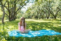 Kvinnan lägger ner eller koppla av på lyssnande musik för grönt gräs med smartphonen i sommar eller fjädrar Royaltyfri Bild