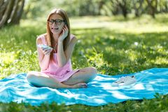 Kvinnan lägger ner eller koppla av på lyssnande musik för grönt gräs med smartphonen i sommar eller fjädrar Royaltyfri Fotografi