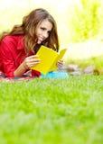 Kvinnan lägger på grönt fält och läser boken. royaltyfri bild