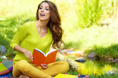 Kvinnan lägger på grönt fält och läser boken. arkivfoton