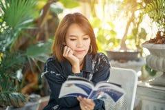 kvinnan läser boken i kaffekafét royaltyfri foto