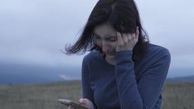 Kvinnan läser dåliga nyheter på en mobiltelefon och gråter i dåligt väder